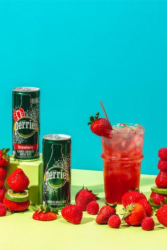 glass of perrier berry smash mocktail with strawberries and cans of perrier