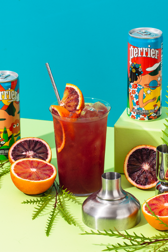 citrus royale mocktail with fresh slices of blood oranges, metal straw, metal mixer and perrier original mineral water