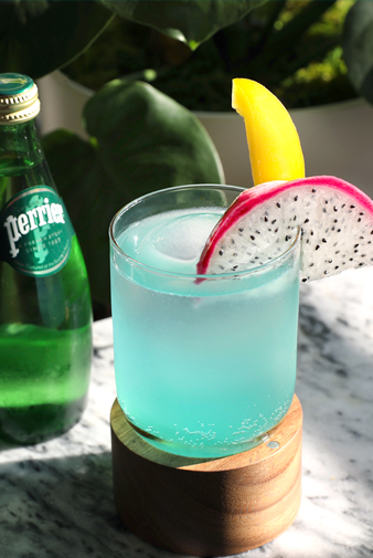 bottle of perrier next to a tequila and blue curacao cocktail with garnish