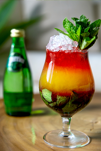 bottle of perrier next to a colorful fruity cocktail with ice and mint sprig