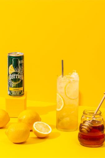 glass of perrier tropical vibes mocktail with cans of perrier and pineapples