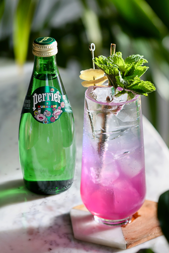 garnished glass of the perrier paradigm mocktail on table next to bottle of perrier